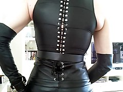 Leather, Mistress wearing leather puts some lube on slave with his ass and fist fucks him